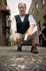 Jimmy Ogle points out unique characteristics of a manhole cover in